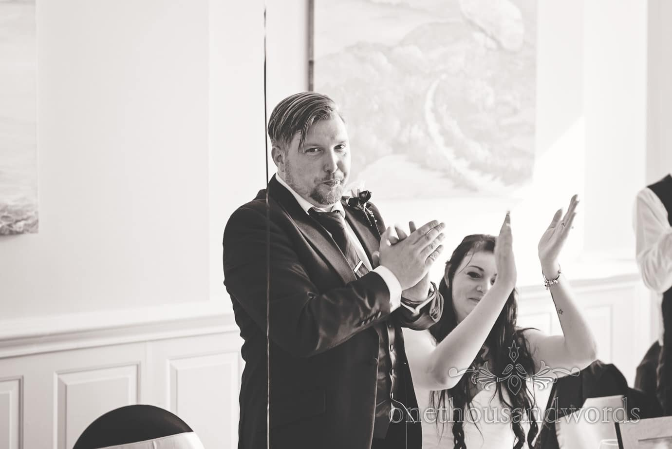 Black and white wedding photograph of bride and groom applauding speeches