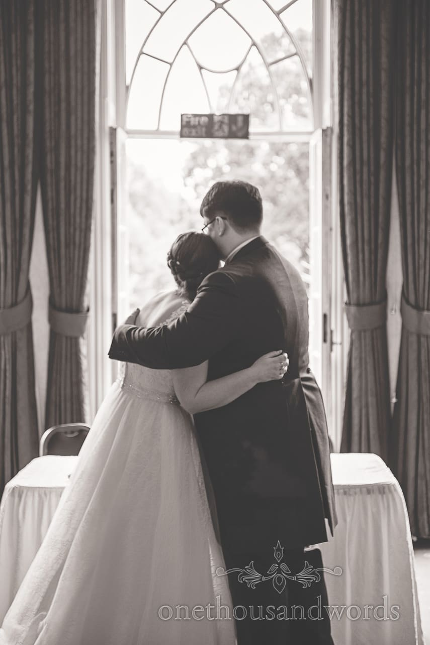 Black and white wedding photograph of bride and groom hugging after ceremony