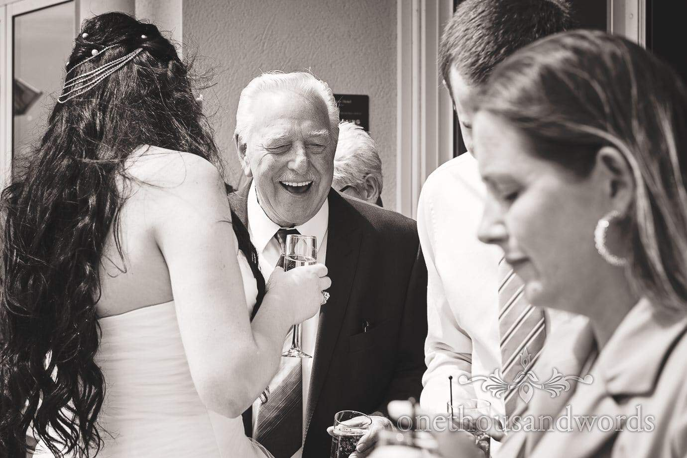 Black and white wedding photograph of elderly wedding guest laughing with bride