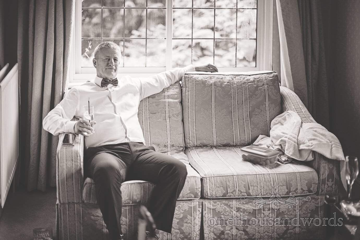 Black and white wedding photograph of father of bride enjoying a gin and tonic during bridal preparations