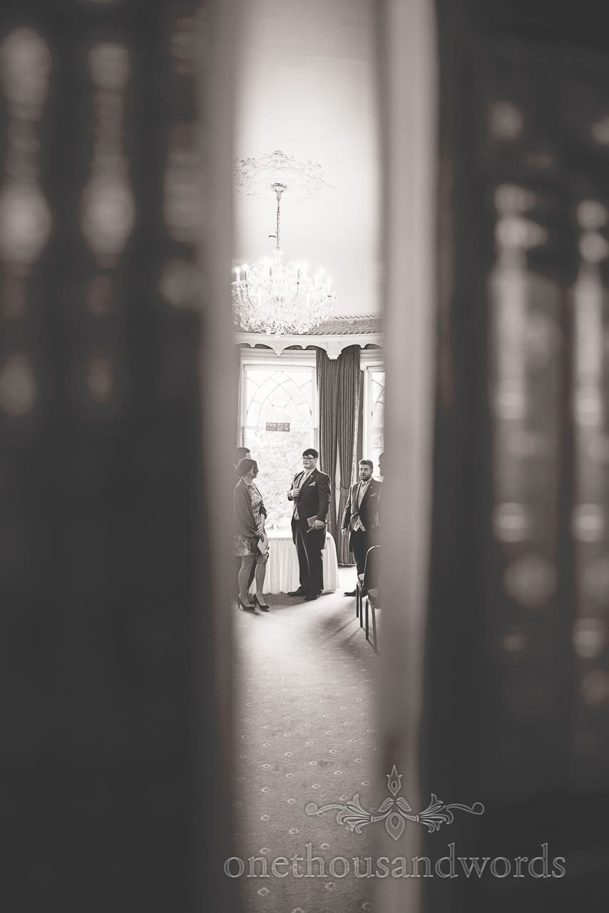 Black and white wedding photograph of groom through Upton House bookshelf