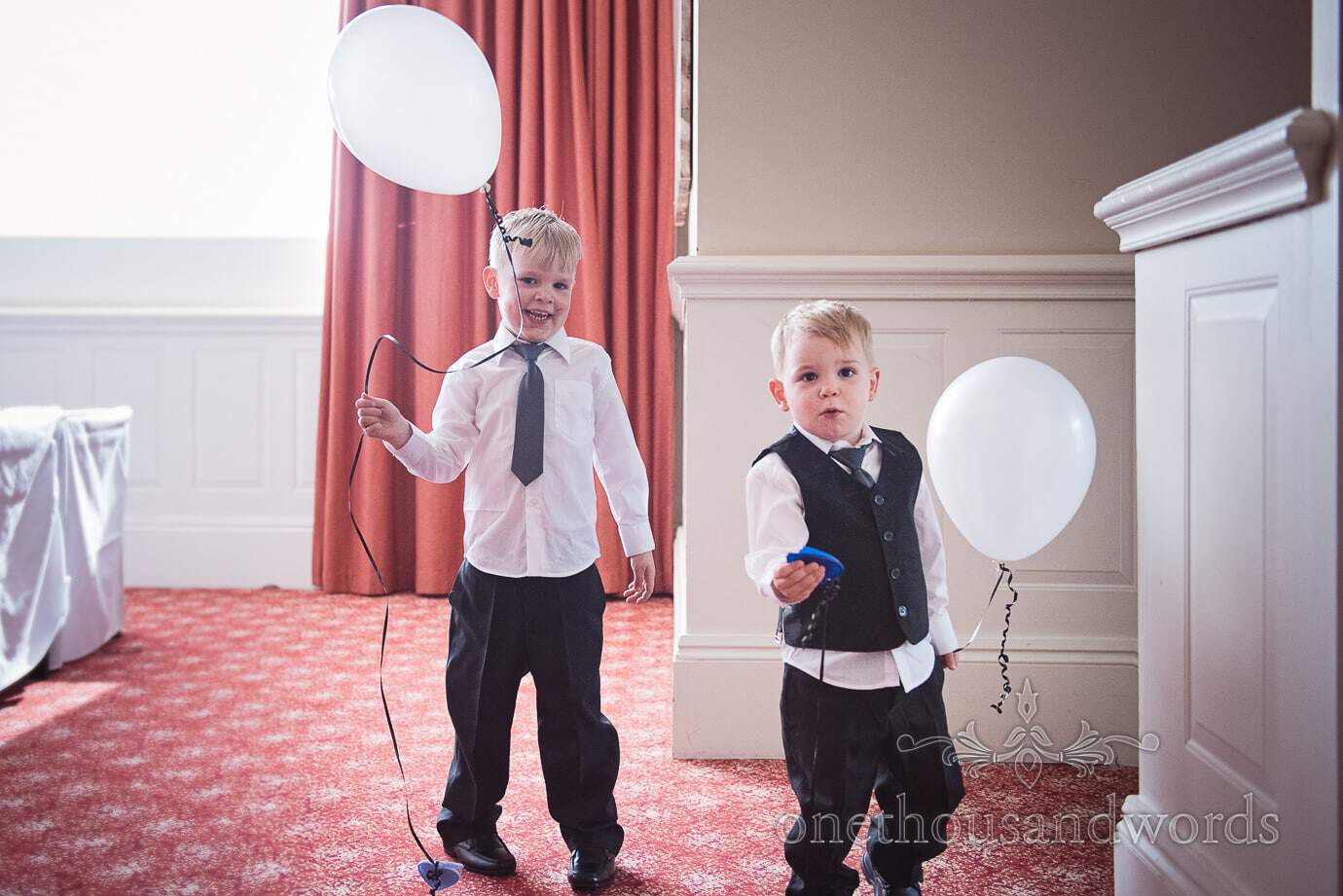 Boys playing with white wedding balloons at black and white themed wedding