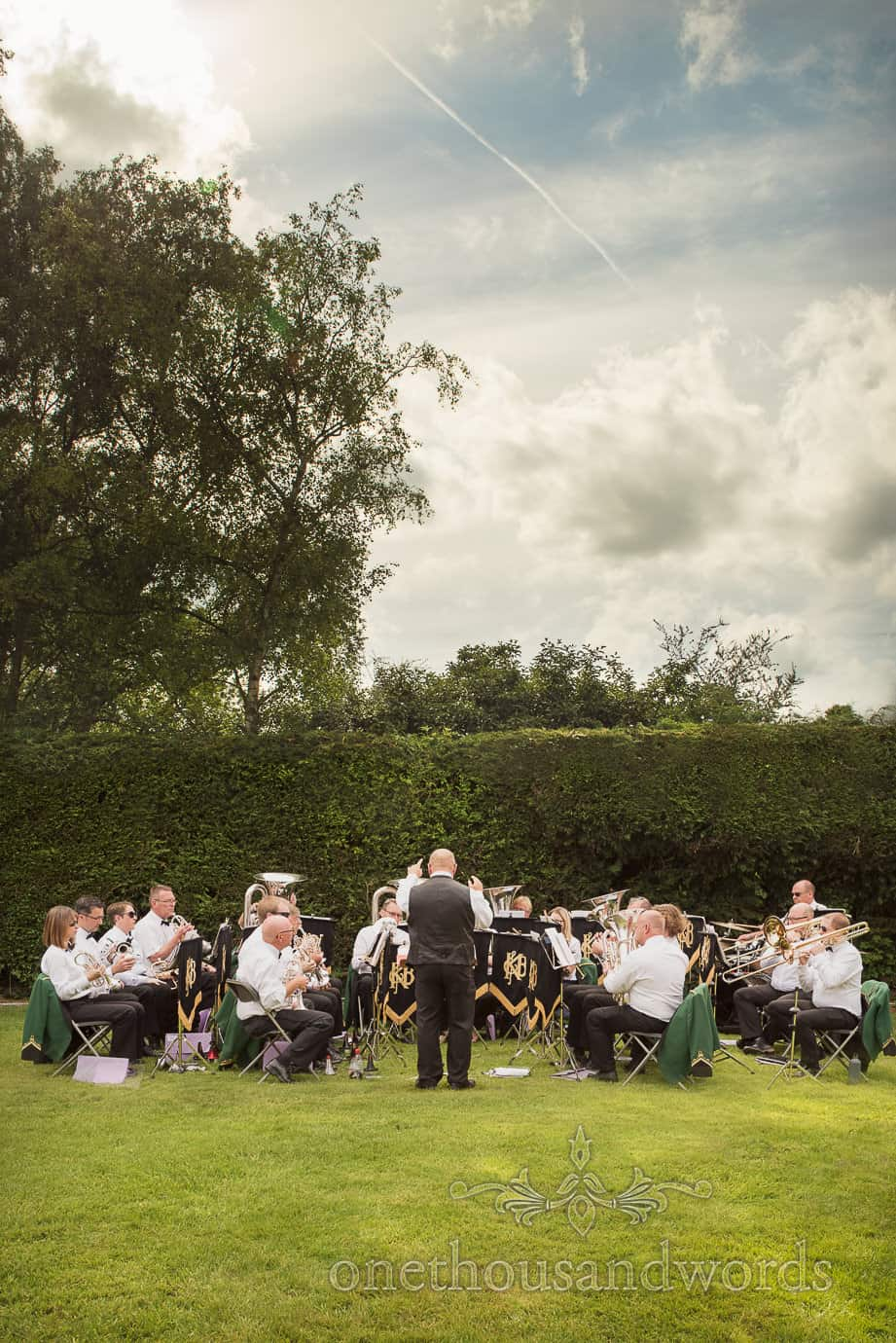 Brass band plays at country wedding in country house gardens