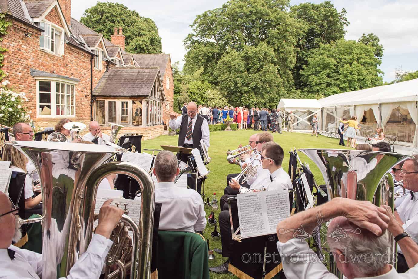 Brass band plays to wedding guests at country house marquee wedding