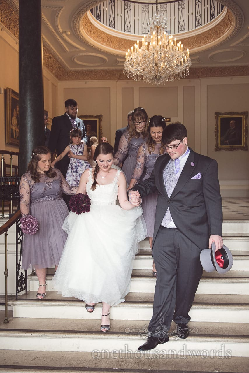 Bridal party descends hallway stone stair case at Upton Country House wedding