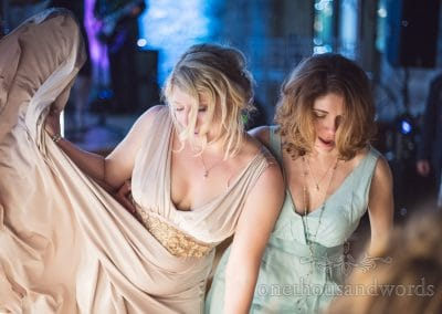 Bride and bridesmaid dancing with flowing dresses at Lulworth Castle wedding in Dorset