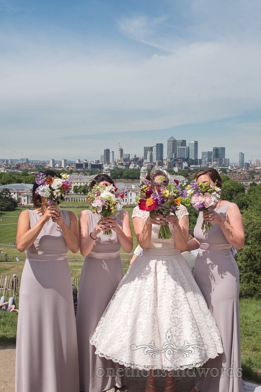 Bride and bridesmaids hold up bouquets with city skyline in distance