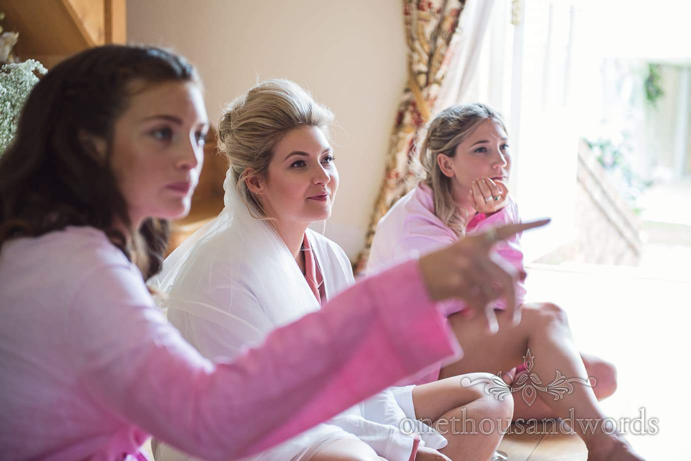 Bride and bridesmaids point to mother of the bride during bridal preparations at home