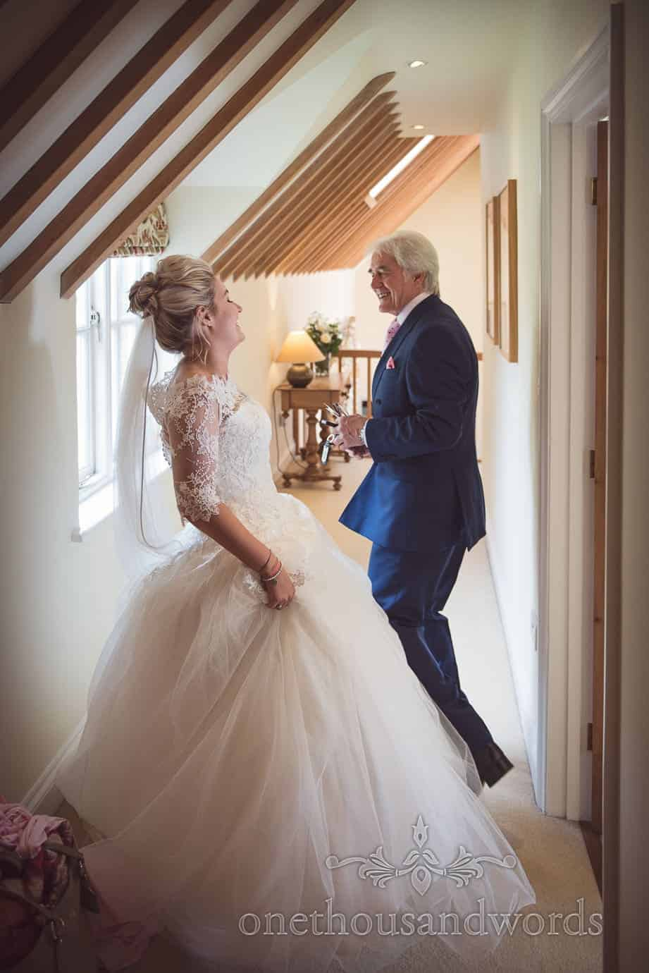 Bride and father laughing together on wedding morning with roofing rafters
