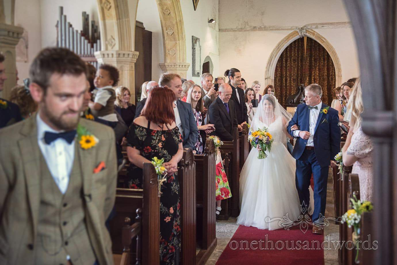 Bride and father of the bride walk down old English stone church aisle during wedding ceremony