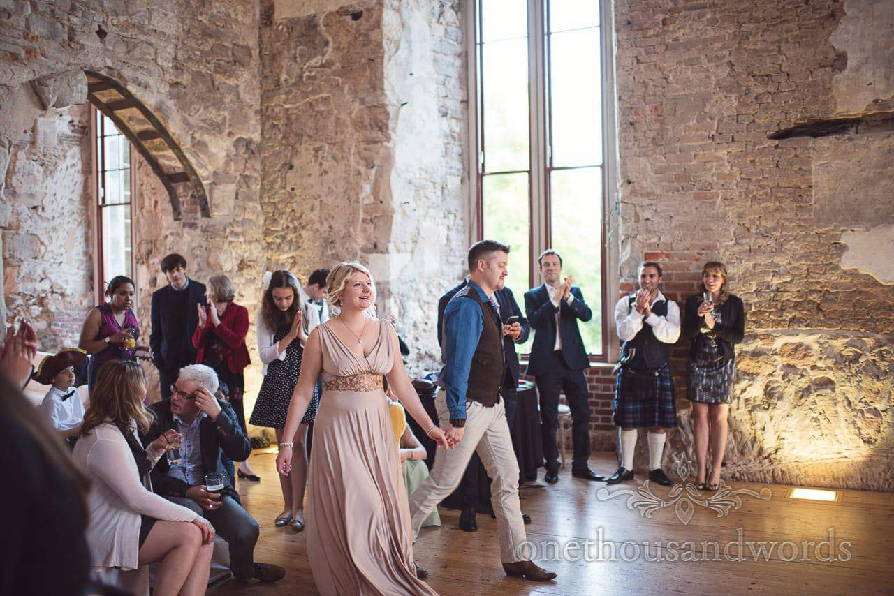 Bride and groom are applauded onto dance floor for first dance in ruined castle venue