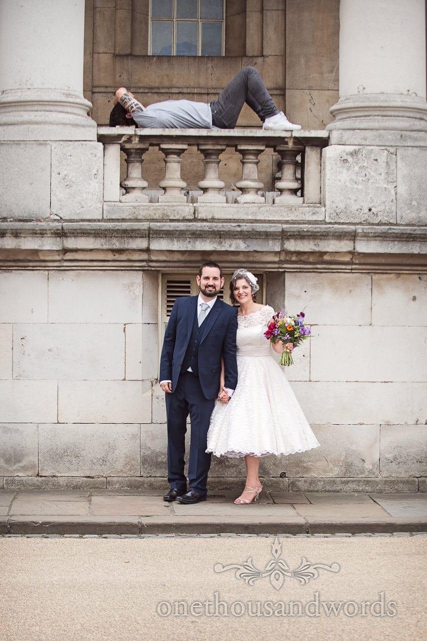 Bride and groom below sleeping man on a hot wedding day in London