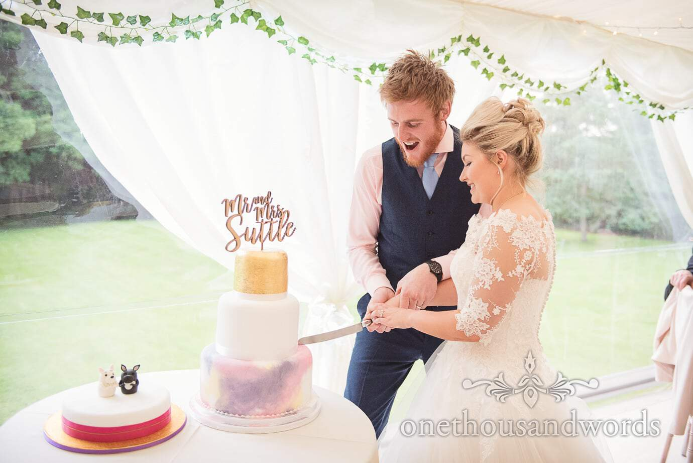 Bride and groom cut colourful wedding cakes in wedding marquee with ivy vines
