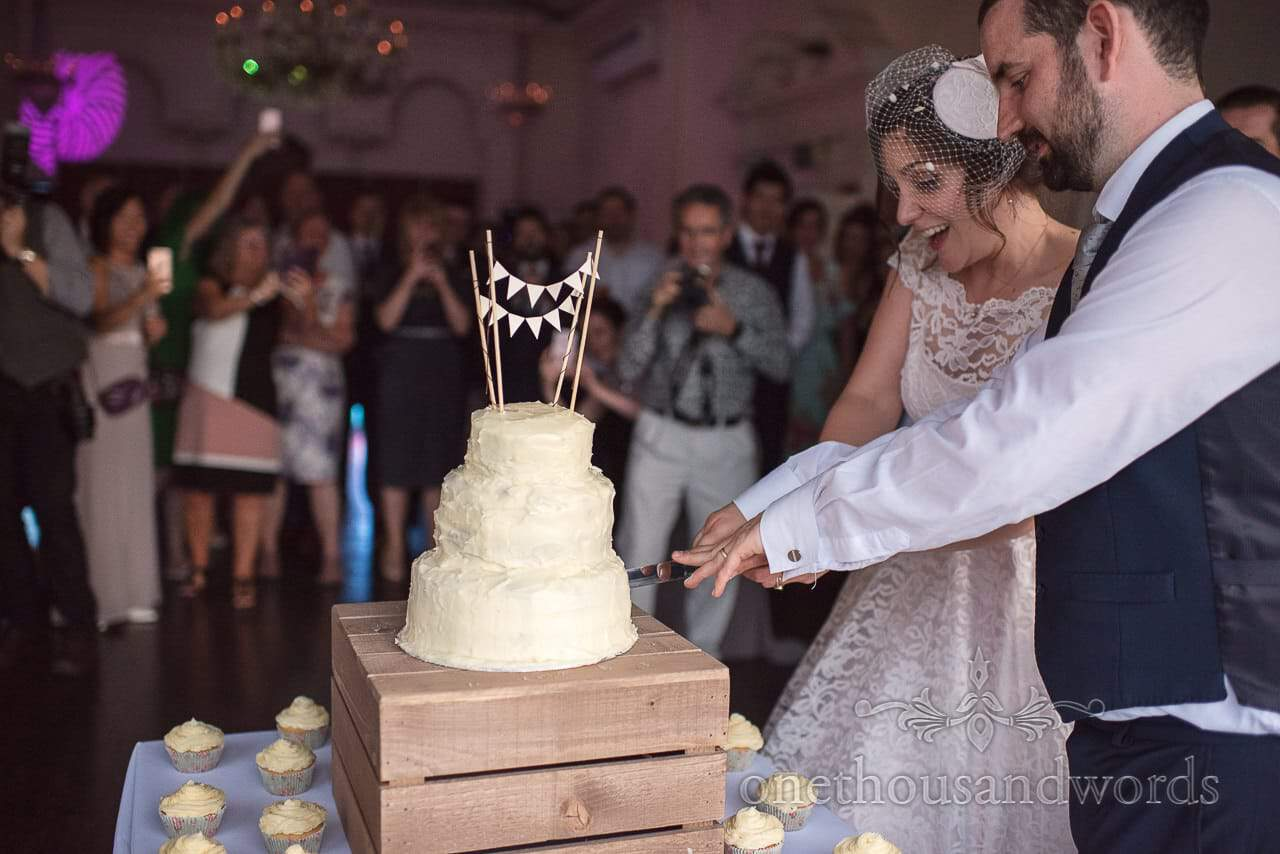 Bride and groom cut wedding cake with mini bunting watched by wedding guests