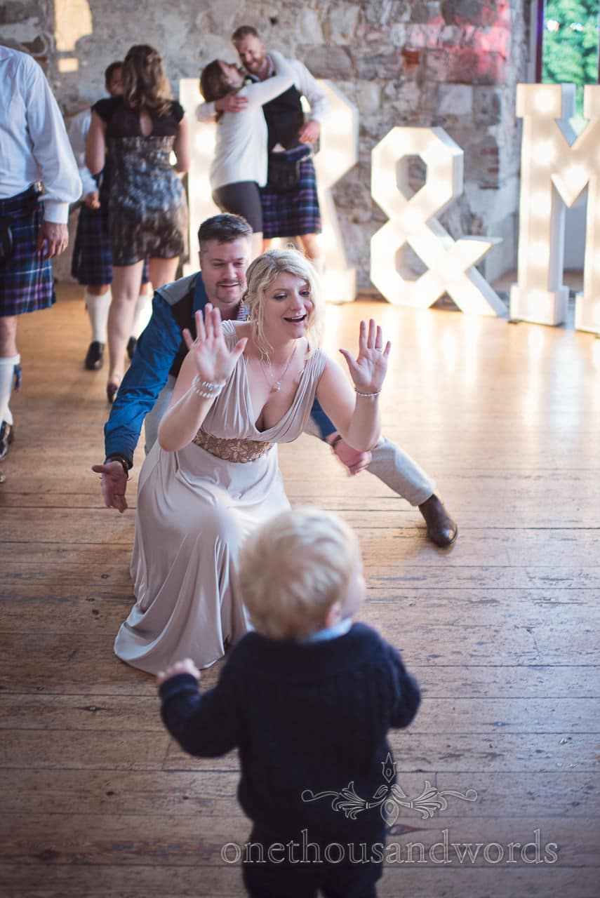 Bride and groom dance with child wedding guest on Lulworth castle wedding dance floor