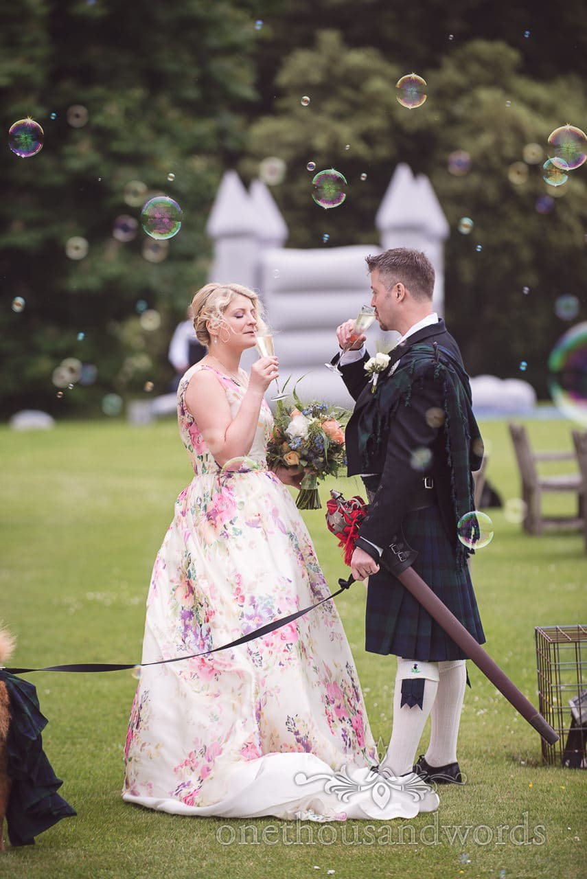 Bride and groom drink champagne with bubbles and bouncy castle in Dorset