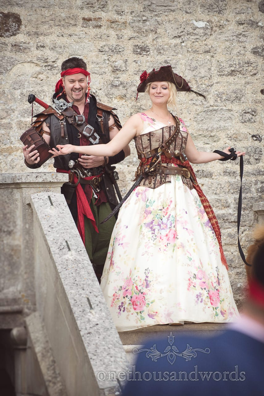 Bride and groom enter pirate themed wedding in amazing pirate fancy dress