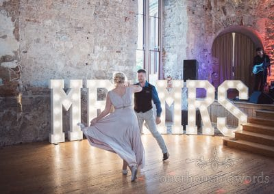 Bride and groom first dance in front of Mr & Mrs light up letters at Lulworth Castle wedding
