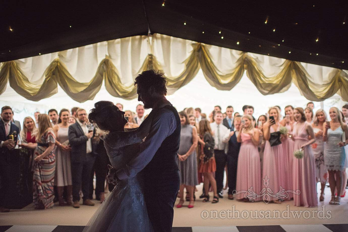 Bride and groom first dance silhouette against marquee reveal and wedding guests