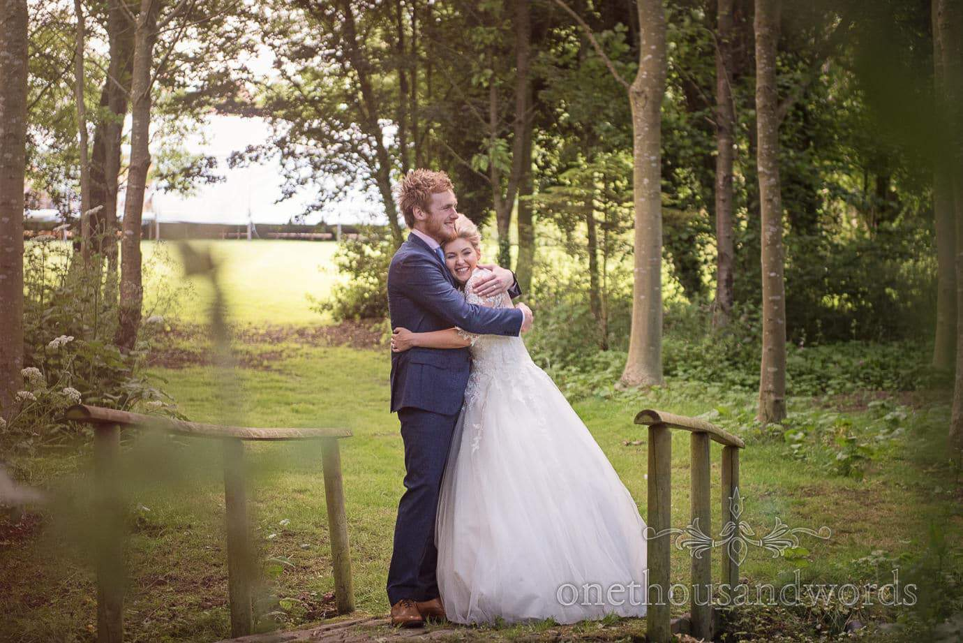 Bride and groom hugging on wooden bridge in woodland at country wedding photographs