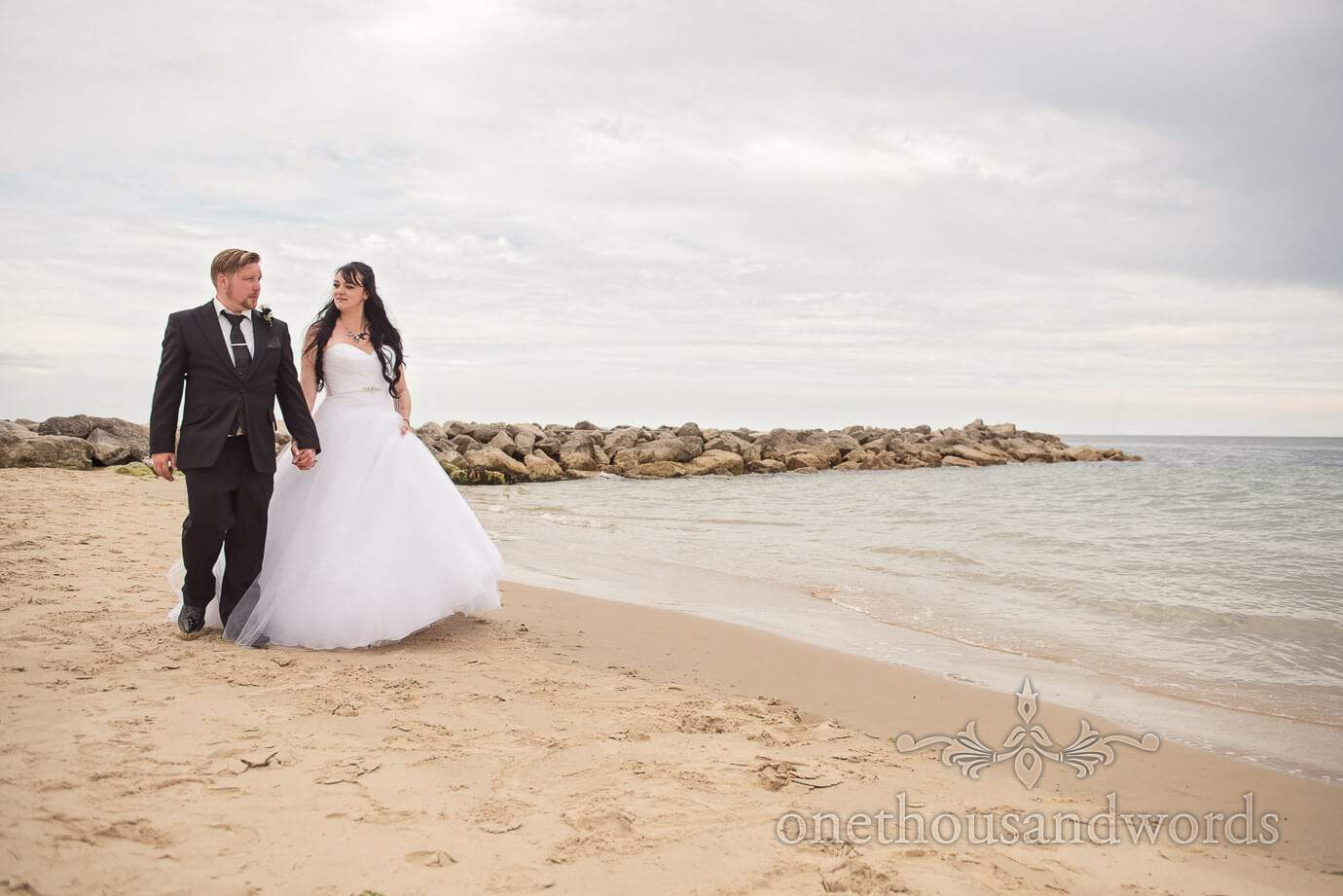 Bride and groom in black and white walk along beach at Rock and Roll wedding by the sea