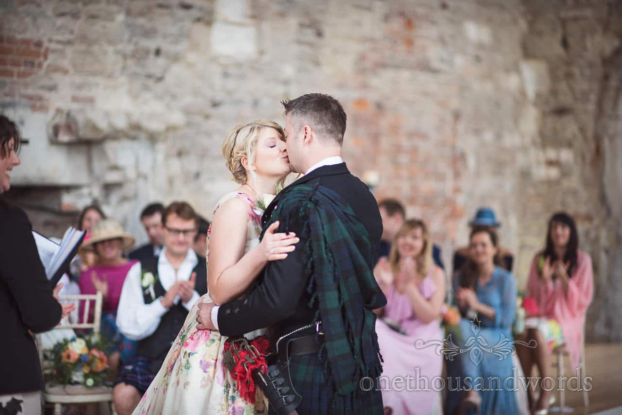 Bride and groom in kilt kiss at ruined castle wedding ceremony in Dorset photograph