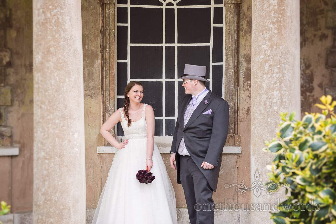 Bride and groom in Top Hat laughing at Upton House wedding venue in Poole
