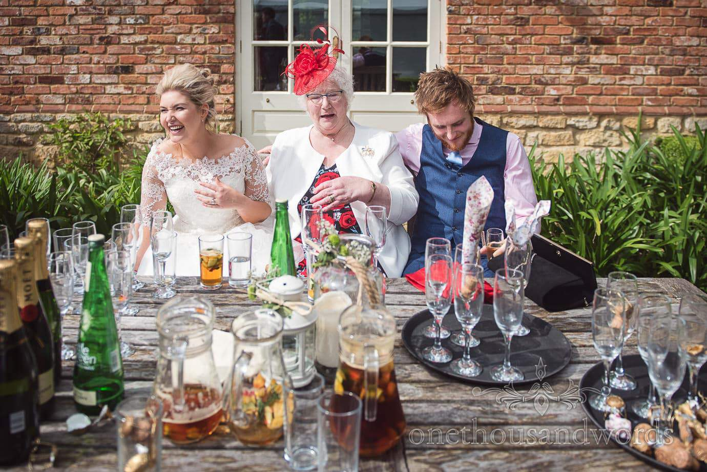 Bride and groom laughing with grandmother at table covered in wedding drinks