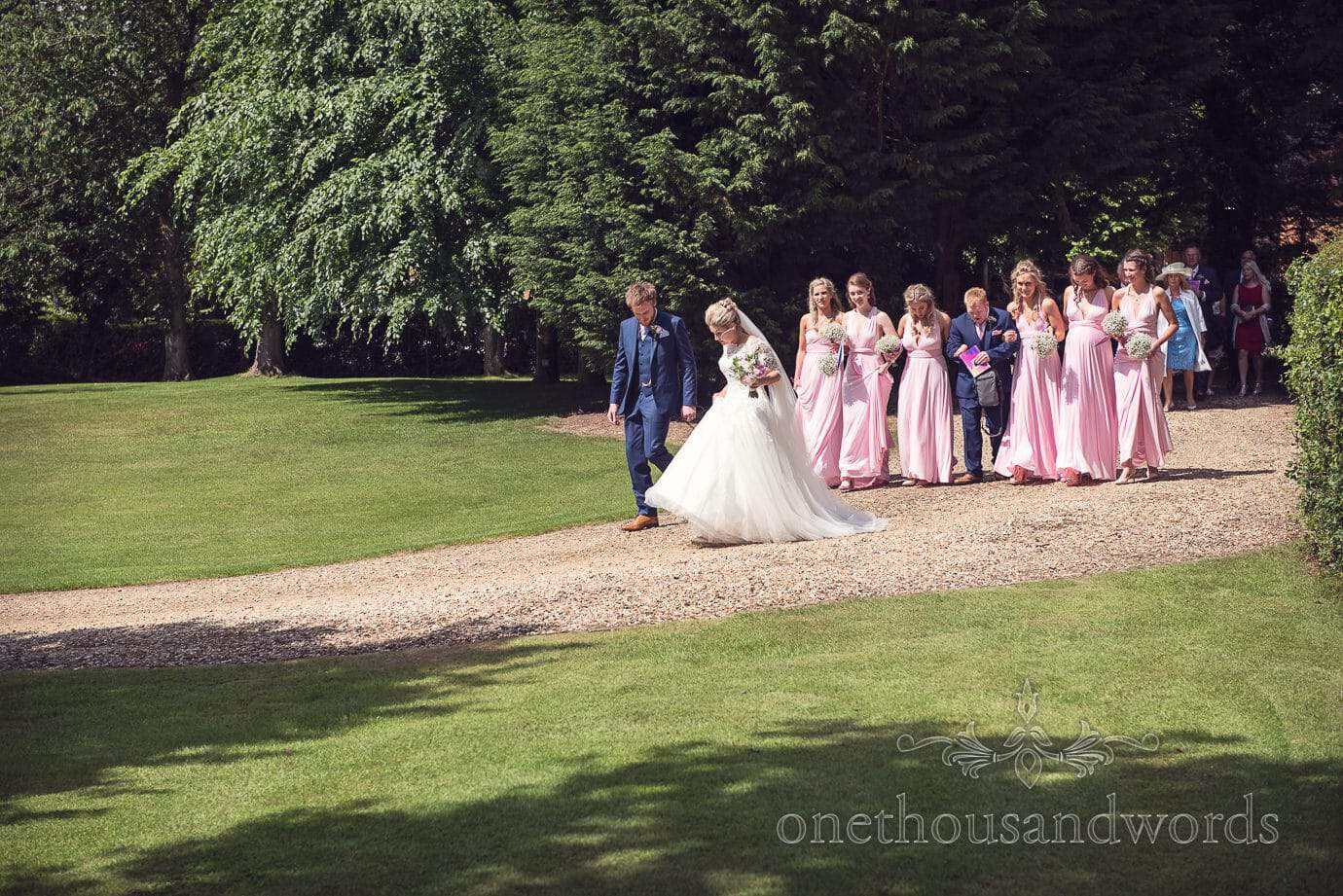 Bride and groom lead bridesmaids in pink and wedding party to country wedding