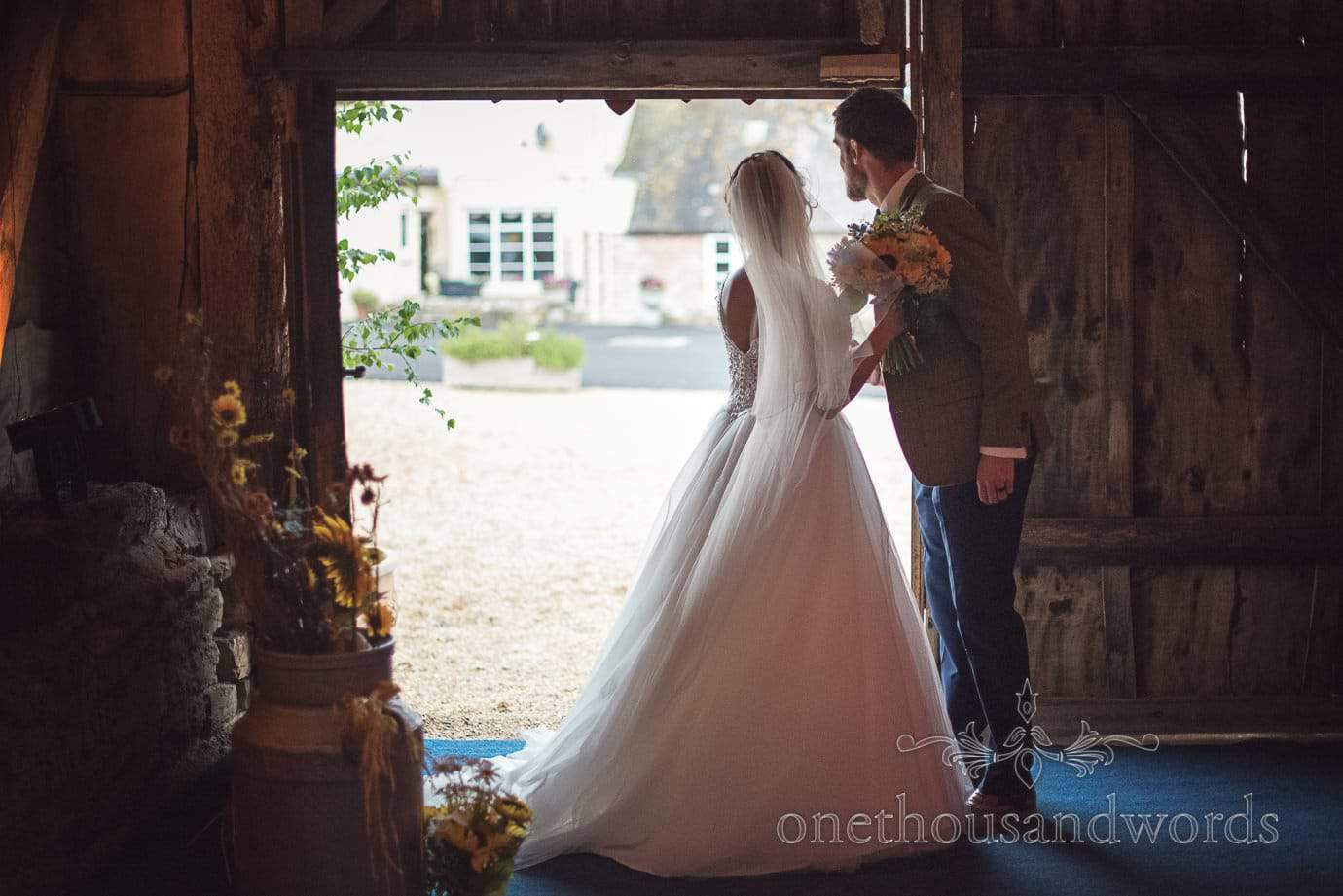 Bride and groom look out the door at rustic barn wedding