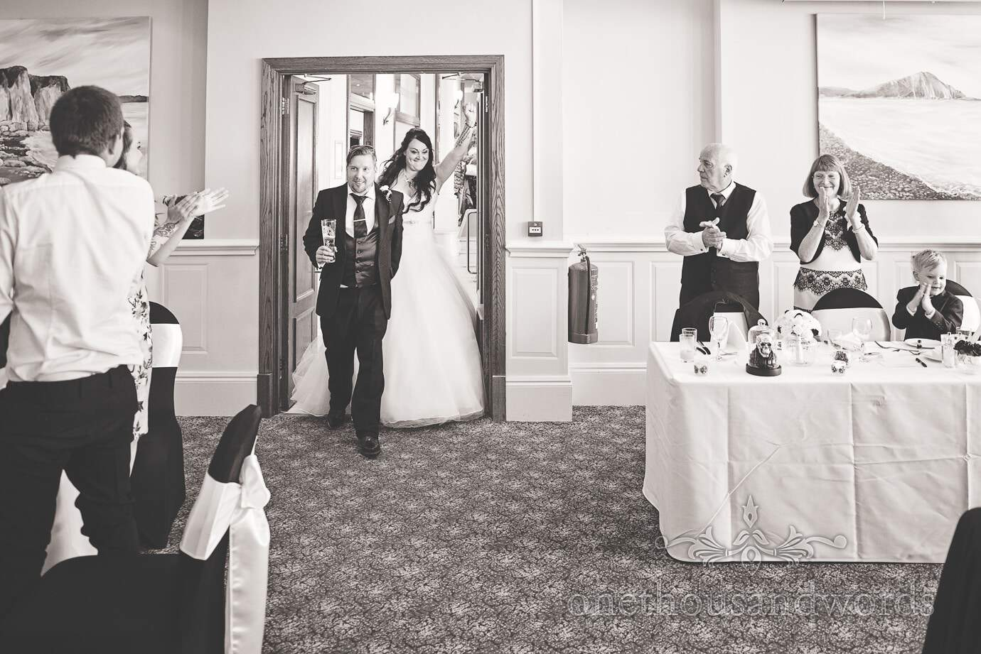 Bride and groom make entrance into wedding breakfast in black and white wedding photograph
