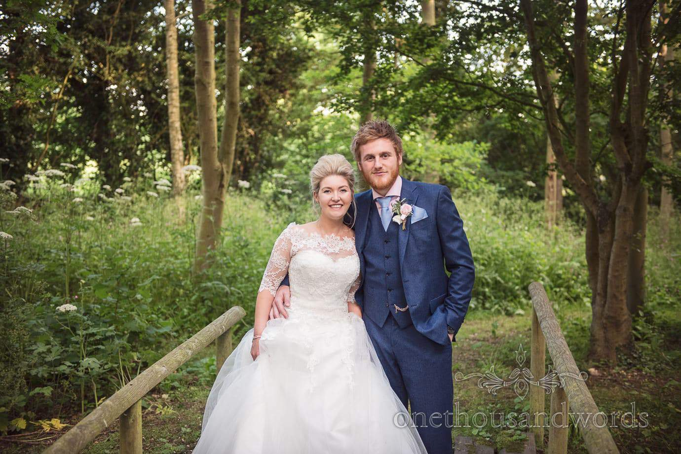 Bride and groom on wooden bridge in country wedding woodland photograph