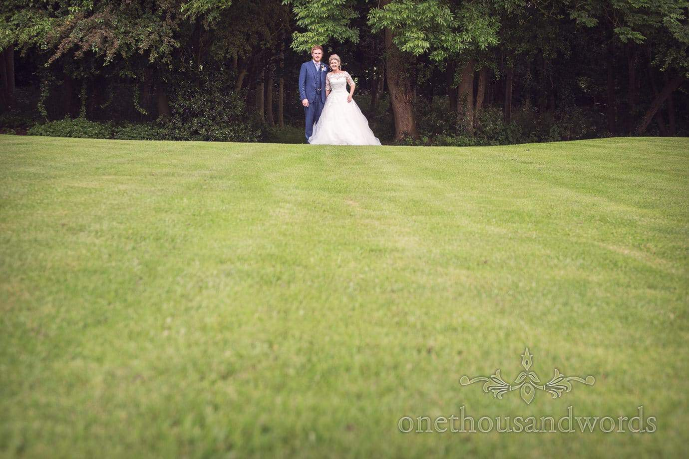 Bride and groom photograph shot across lawns at country wedding in Leicestershire