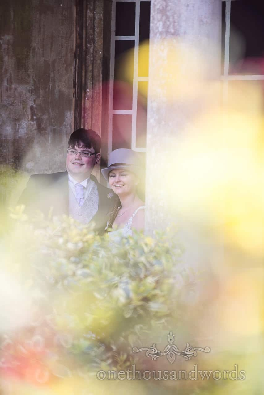 Bride and groom photographed through flowers at Upton House wedding venue