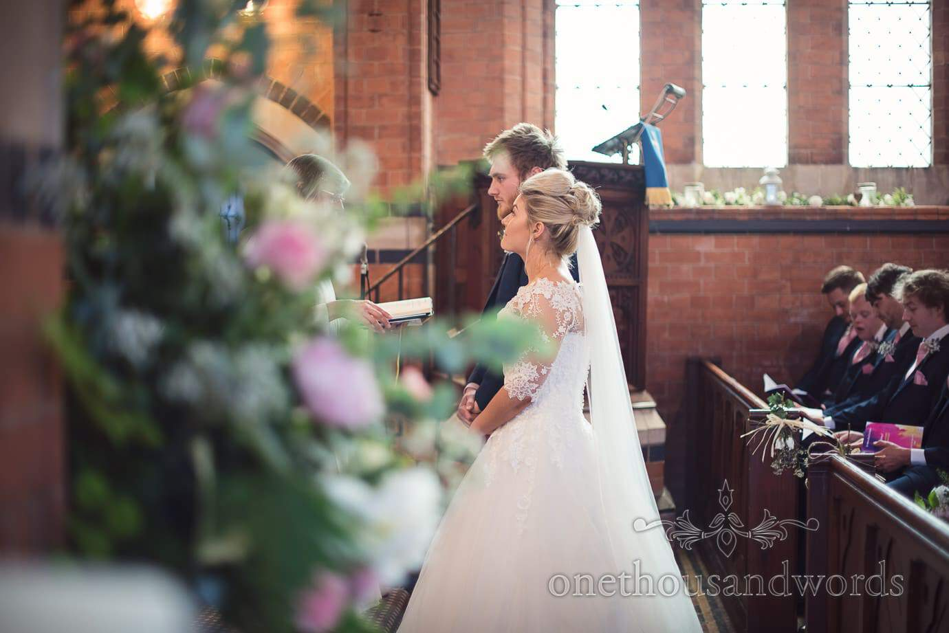 Bride and groom photographed through wedding flowers in church