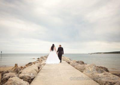 Bride and groom walk down stone groyne at Dorset sea side wedding at Haven Hotel