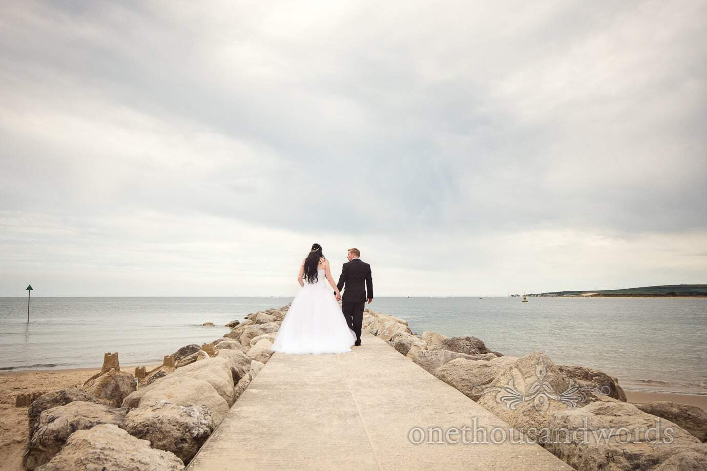 Bride and groom walk down stone groyne at Dorset sea side wedding at Haven Hotel