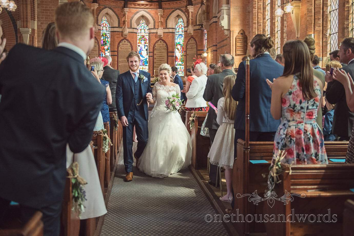 Bride and groom walk down the aisle together in red brick country church