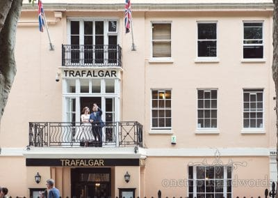 Bride and groom wave to public on balcony at Trafalgar Tavern wedding venue