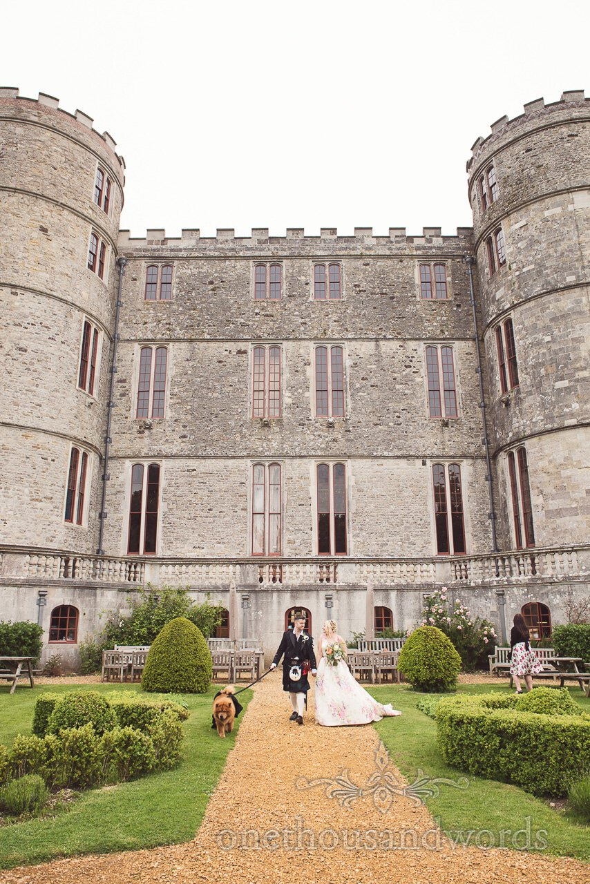 Bride and groom with dog walk through the grounds of Lulworth Castle wedding venue