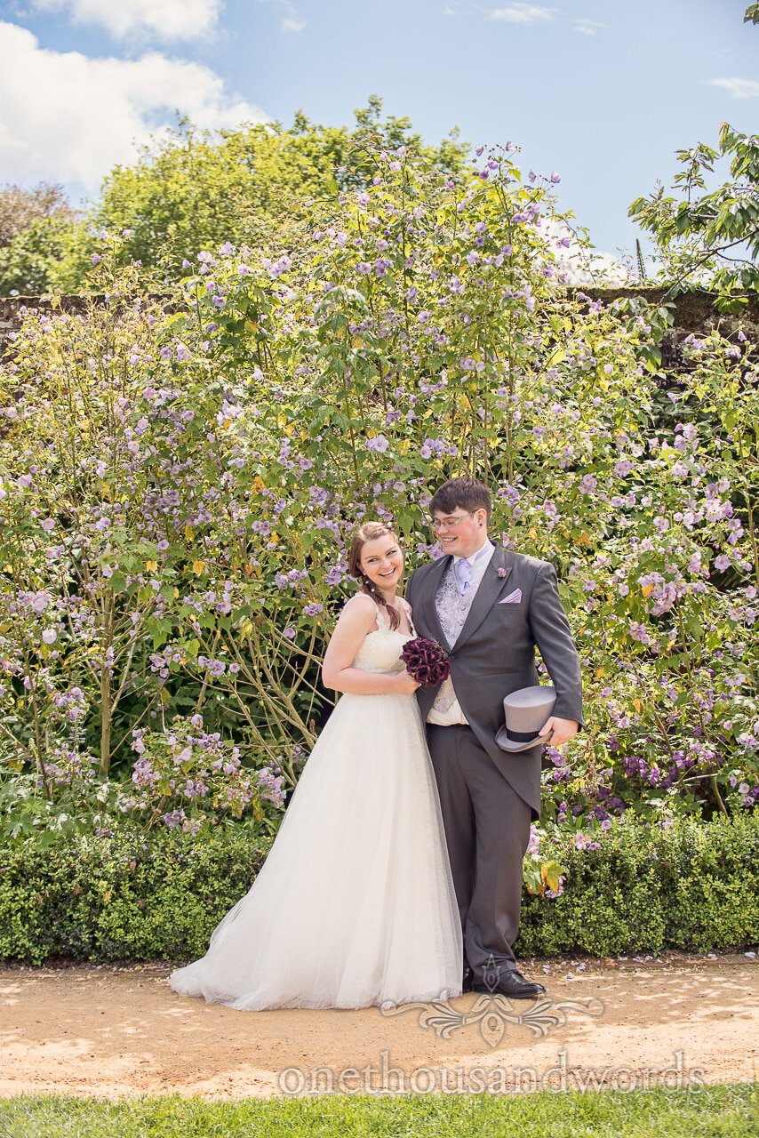Bride and groom with violet flowers at Upton Country Park gardens wedding venue