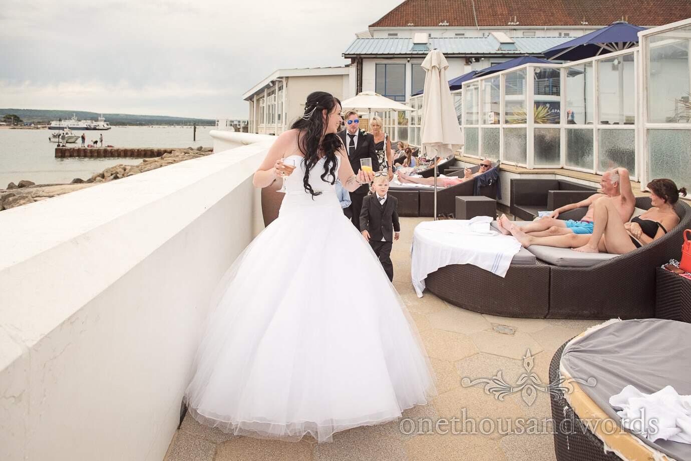 Bride and wedding party walk past Hotel spa guests sunbathing by the sea in Sandbanks