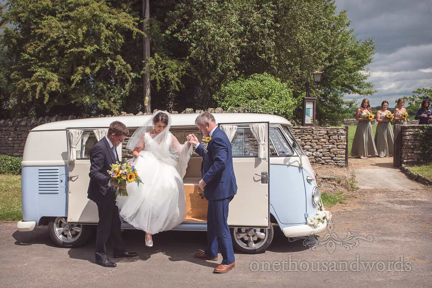Bride arrives at church in classic VW wedding transport under stormy skies with bright sunshine