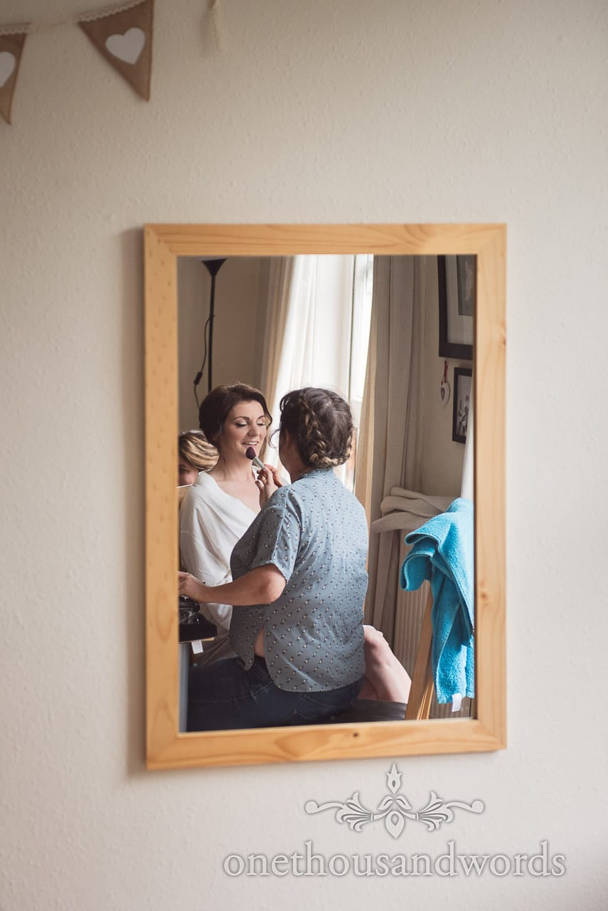 Bride being made up in mirror at Greenwich wedding photographs