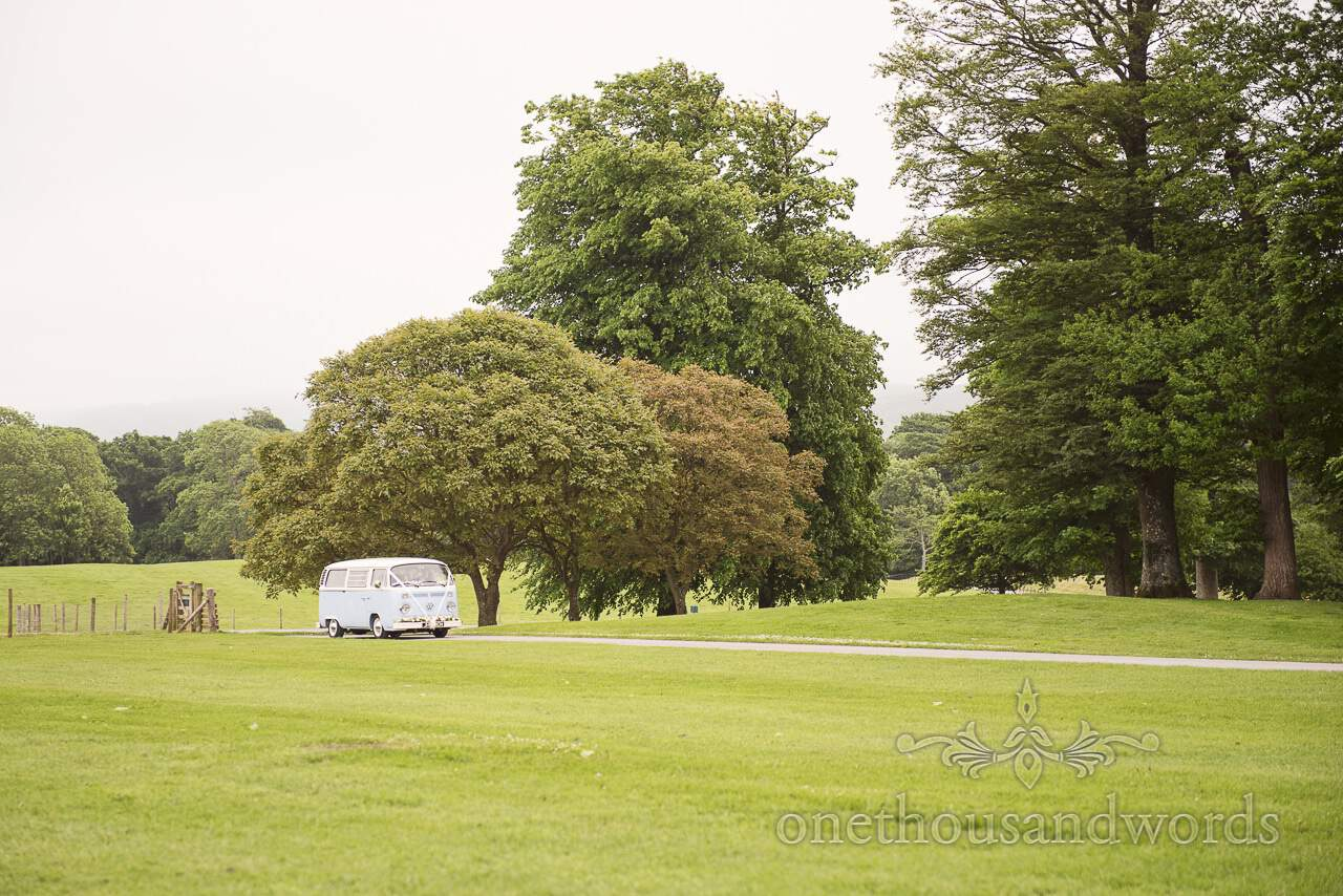 Bride comes up the driveway in Volkswagen but at Lulworth castle wedding