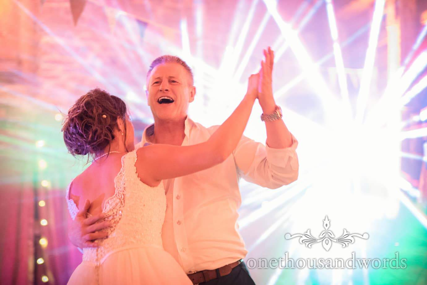 Bride dances with father against disco lights at barn reception