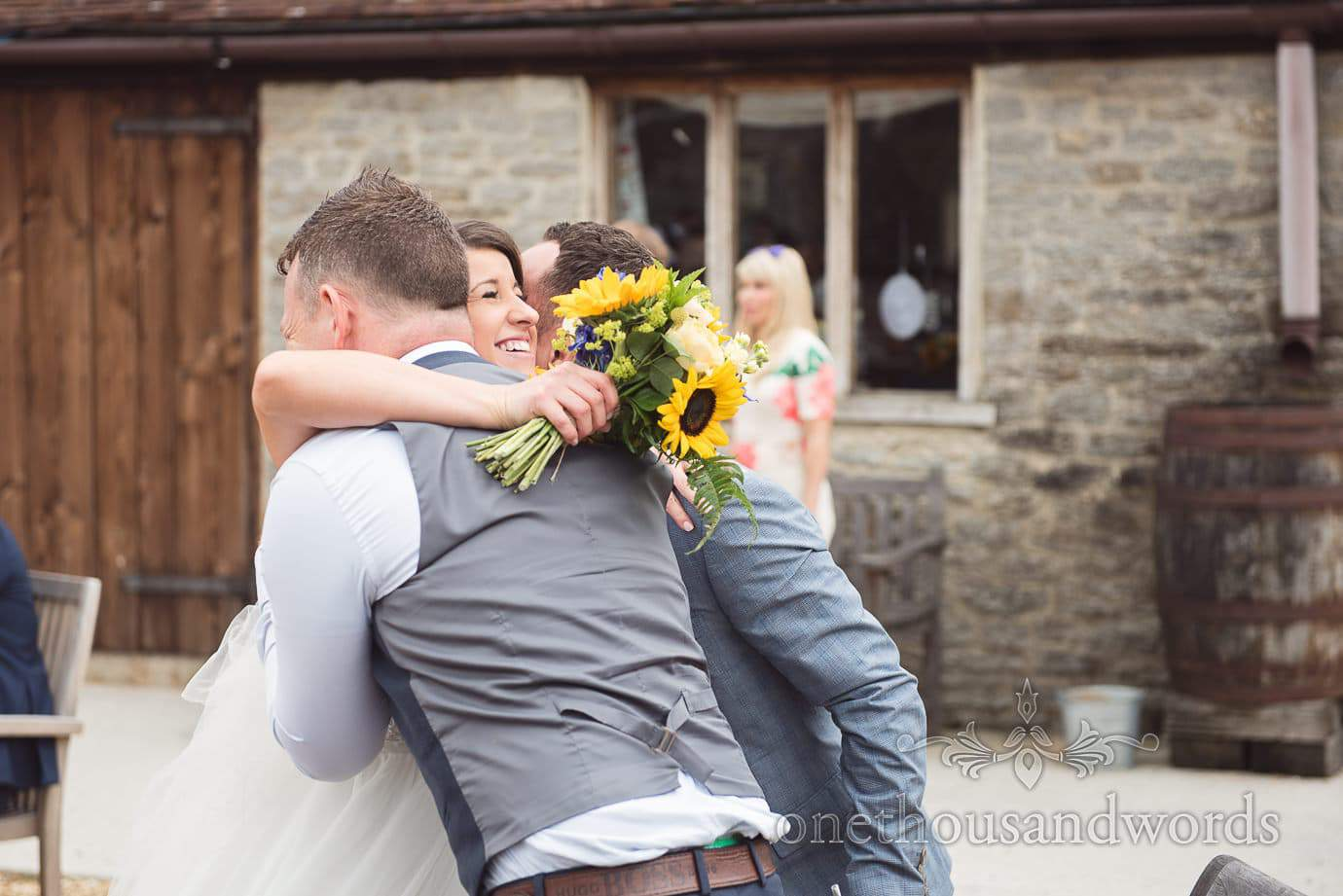 Bride embraces two guests with her sunflower wedding bouquet at rustic barn wedding