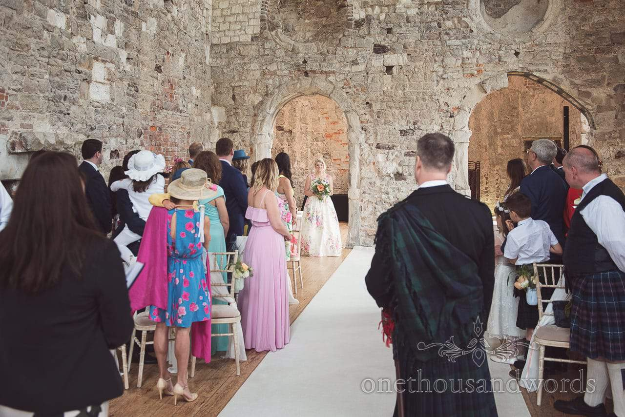 Bride enters wedding ceremony in ruined stone castle wedding venue in Dorset