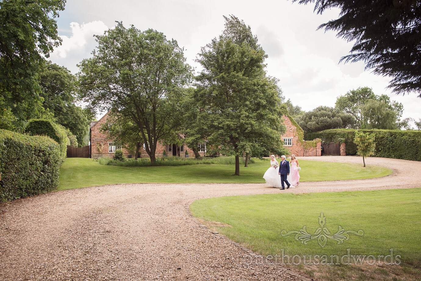 Bride, Father and Bridesmaid walk from family country house to church wedding