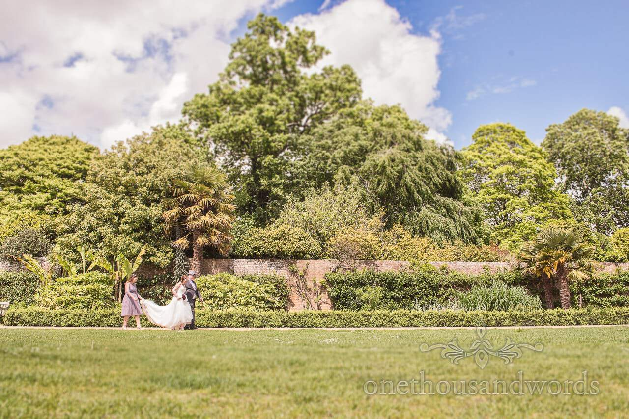 Bride, groom and bridesmaid walk though Upton Country House gardens